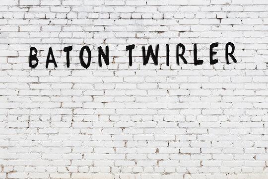 White wall with black paint inscription baton twirler on it
