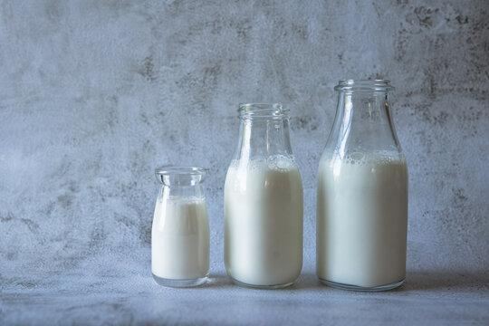 Three glass bottles of milk on a grey background