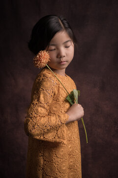 Teenage girl holding dahlia flower while standing indoors