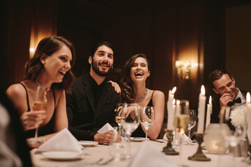 Socialites sitting around a dining table at a party