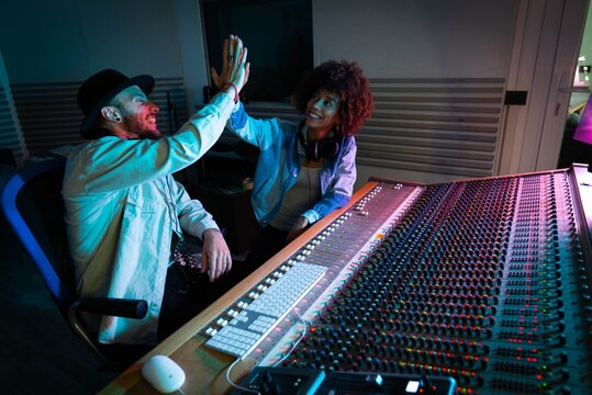 A professional male producer and young african female singer are happy with results of recording a new song and  are celebrating a future success in a music studio with colorful lights on a background