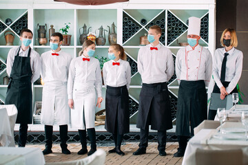 Employees of a Restaurant or Hotel in protective masks. End Of Quarantine. Restaurant Manager and his staff on the terrace. interaction with the chef in the restaurant.