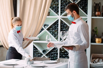 A waiter in a medical protective mask serves a table in the restaurant. Employees of a restaurant...