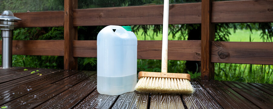 Brush and plastic canister with detergent on a wooden board, wooden terrace. Technologies and tools for cleaning surfaces.