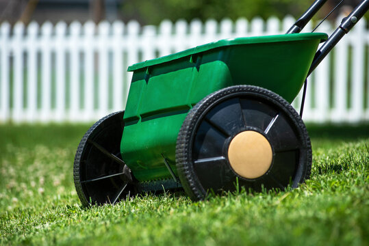 Close-up isolated lawn chemical grass seed and fertilizer spreader in yard with white picket fence in background