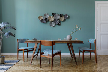 Modern and stylish dining room interior with glamour wooden table , elegant chairs and design decoration. Template. Home decor.  Minimalistic concept of interior design.