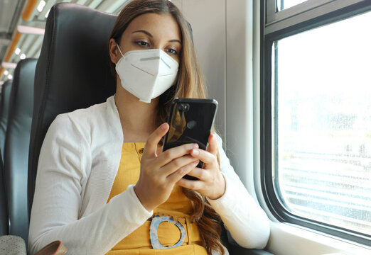 Relaxed woman with KN95 FFP2 face mask using smart phone app. Train passenger with protective mask traveling sitting in business class texting on mobile phone. Travel safely on public transport.