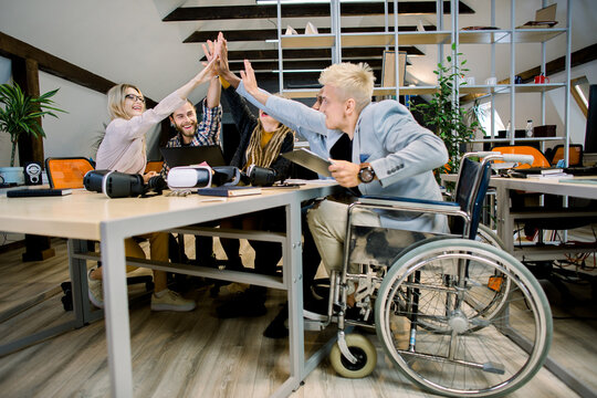 Happy multiethnic diverse young people sitting in office and giving high five each other after great collaboration, discussing strategies. Disabled male manager sitting with his colleagues at office