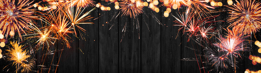 Festive Silvester Party background banner panorama long- Frame made of red orange golden firework and bokeh lights on dark black grey wooden wall texture, with space for text