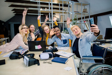 Handsome joyful man in wheelchair sitting at desk with his colleagues, and making funny selfie photo on smartphone. Group of multiethnic hipster coworkers posing for photo and waving