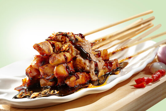 Satay smothered in peanut sauce, soy sauce, and fried onions, decorated with peeled onions and sliced red chillies.