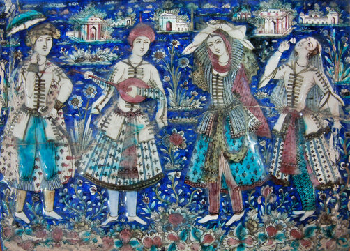 Ceramic tiles of 19th century house wall with dancing people and musicians in garden. Iran.