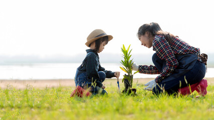 Asian  kid daughter helping mother water and sapling  the plant tree outdoors in nature spring