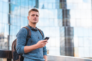 Pensive man using phone portrait with modern buildings on background - Thoughtful man alone in the city - Lifestyle and business concepts in capital city