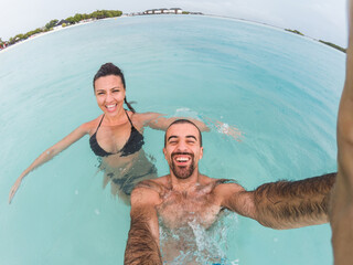 Happy couple taking a candid selfie at Maldives resort and enjoying seaside under the rain - Smiling and laughing young people at summer destination - Tropical beach vacation at ocean paradise