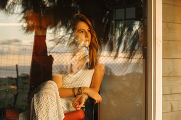 Serene female in knitted summer dress sitting in cozy armchair near window and admiring picturesque sunset while enjoying vacation in wooden cabin