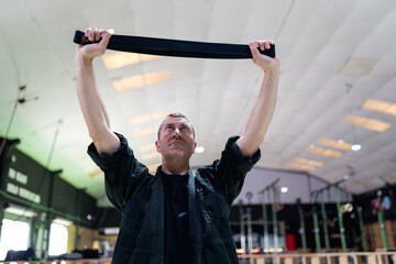 Low angle of serious adult man in black wear performing exercise with resistance band during kajukenbo training in modern martial arts gym