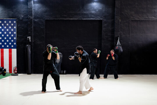 Side view of concentrated male martial arts practitioners in black kimono fighting with gloves during kajukenbo workout in modern club