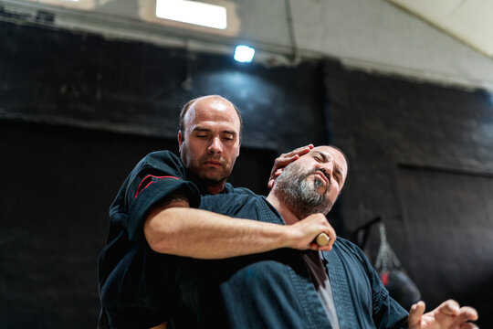 Low angle of kajukenbo trainer and student practicing fighting choke technique with stick during martial arts training in modern club