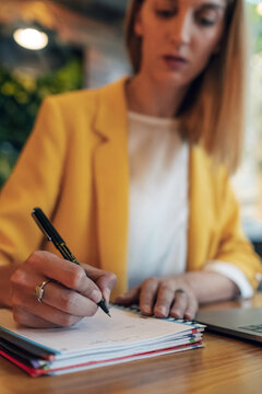 Blurred businesswoman in elegant colorful clothes writing with pen in notebook while sitting at wooden table and using laptop in light contemporary office