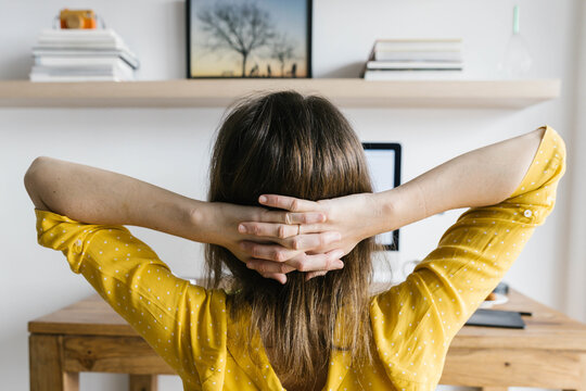 Back view of unrecognizable female freelancer in yellow shirt sitting on desk and holding hands behind head while resting during working on computer at home on daytime