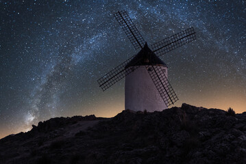 Low angle of spectacular landscape of rocky mountain with traditional windmill on background of amazing Milky Way in dark sky
