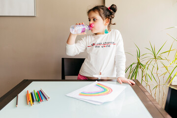 Positive girl in casual clothes drinking water from plastic bottle while standing near wooden table and drawing picture with colored pencils at home