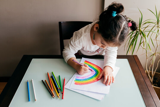 From above of anonymous girl in casual clothes sitting on chair at wooden table and drawing colorful rainbow with pencil on paper