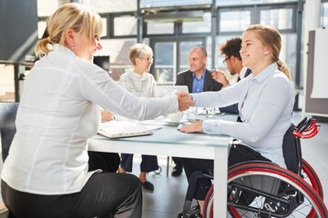 Businesswoman and colleague in wheelchair doing handshake