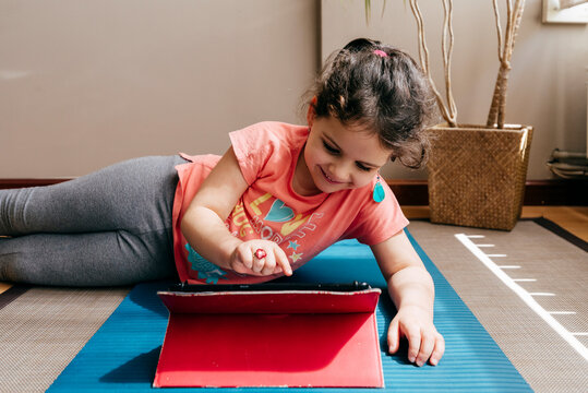 Positive little girl lying down on mat near window at home resting after practicing yoga throughout video tutorials on tablet