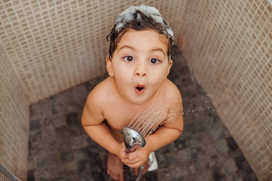From above smiling little child with foam on head standing in bathroom with shower and singing while looking at camera