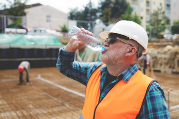 Portrait of a worker, an engineer resting and drinking water after hard work on a construction site