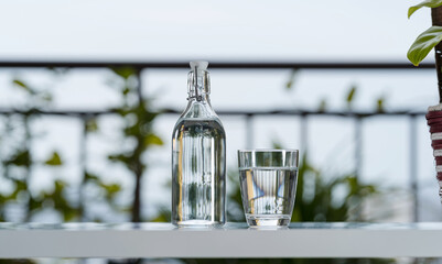 Drink water bottle with glass on table at garden home