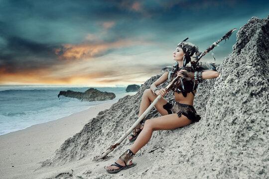 Amazon woman with staff enjoying sunset on the ocean