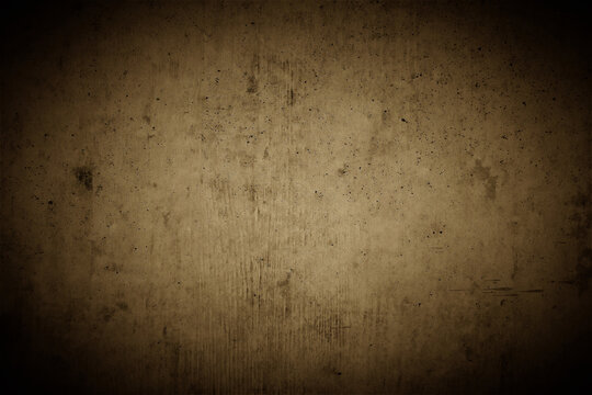 Old brown concrete wall with strong dark vignette as a highlighting background in a rustic industrial design with space for text and logos.