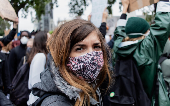 Attractive young female attending a protest against racism while wearing a reusable face mask during coronavirus outbreak
