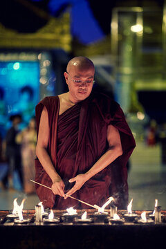 Portrait of buddhist monk lights a candles