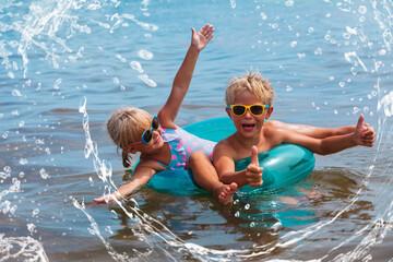 happy boy and girl splash water on beach, kids summer fun