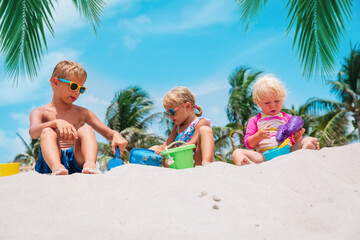 kids play with sand on beach, boy and girls on tropical vacation