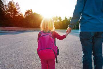 father and little daughter coming from school or daycare
