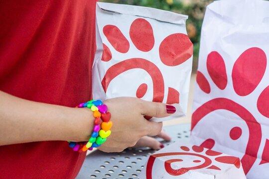ATLANTA, UNITED STATES - Jul 26, 2019: Gay lesbian lgbt lgbtq hands holding Chick-fil-a southern fried chicken sandwich