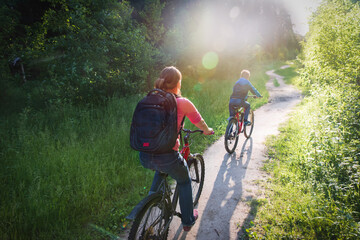 mother and son riding bikes in sunset nature
