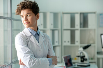 Pensive middle-aged female researcher in lab coat standing with crossed arms and looking back while thinking of new experiment