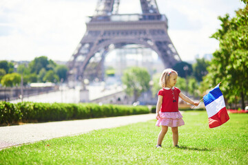 toddler girl with French national tricolor flag near the Eiffel tower in Paris, France