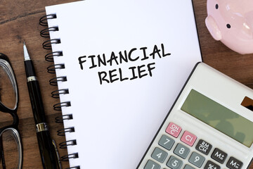 Financial Relief text on note pad with calculator and piggy bank