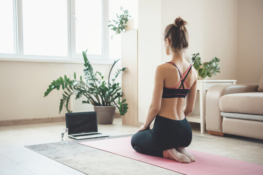 Back view photo of a caucasian sporty woman in sportswear meditating in front of laptop on the floor