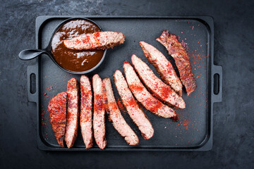 Traditional barbecue sliced dry aged wagyu flank steak offered with spicy BBQ Sauce and chili powder as overhead view on a modern design cast-iron tray