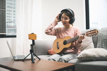 Asian woman blogger recording and live steam playing guitar on social media. Concept of guitarist online lesson while staying at home