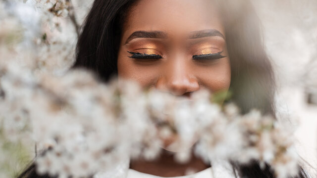 Close-up face of a beautiful happy african black woman with closed eyes in flowers on a spring blooming day. Happy young afro girl with a great mood, warm emotions
