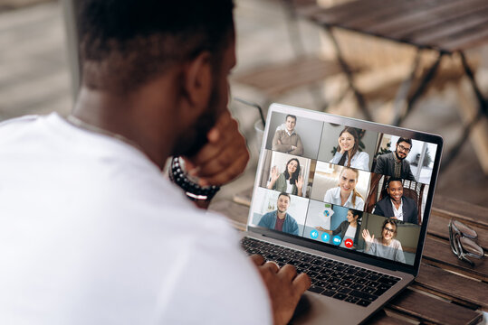 Video call. Video conference. Successful African American freelancer communicate by a video conference with his colleagues using a laptop while sitting in cafe in a summer terrace